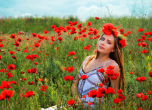 Girl walking in poppy field. Side view of girl walking in poppy field Royalty Free Stock Images