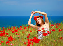 Girl walking in poppy field. Side view of girl walking in poppy field Royalty Free Stock Photo
