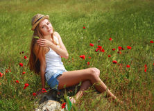 Girl walking in poppy field. Side view of girl walking in poppy field Royalty Free Stock Photography