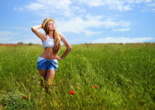 Girl walking in poppy field. Side view of girl walking in poppy field Stock Photography