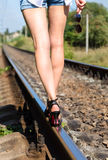 Girl walking on railroad holding sunglasses in hand Royalty Free Stock Photos