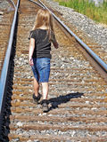 Girl walking on railroad tracks Stock Photos