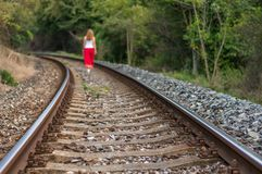 Girl walking on rails Stock Photo