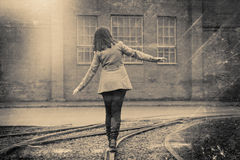 Girl walking on the railway, retro stylized photo. Girl walking on the railway, retro stylized in black and white colors photo Stock Image
