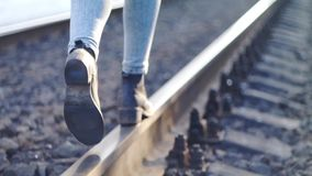 Girl walking on the railway track.  stock footage