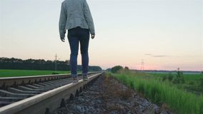 Girl walking on the railway track. Spring evening, video stock footage