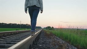 Girl walking on the railway track. Video stock video footage