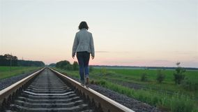 Girl walking on the railway track. Video stock video