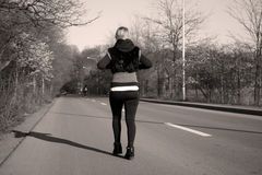 Girl walking on the road Royalty Free Stock Image