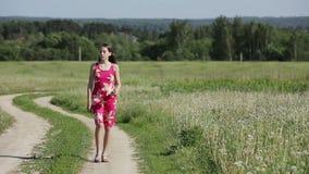 Girl walking by road in field stock video footage