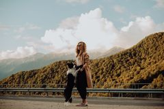 Girl walking on the road with his dog in the mountains stock image