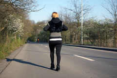 Girl walking on the road Stock Photos