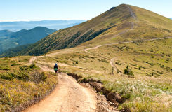 A girl walking a road towards a mountain peak. In late summer. The Carpathian mountains, Svydovets ridge Stock Photos