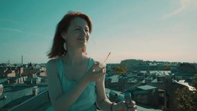 Woman on the roof. Girl walking on the roof and blowing bubbles stock footage