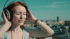 Woman on the roof. Girl walking on the roof and listens to music stock video footage