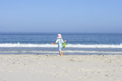 Girl (3-5) walking on sandy beach with bucket and spade, rear view, sea in background Royalty Free Stock Photo