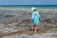Girl walking into sea. Girl in blue hat and dress walking into sea Royalty Free Stock Photography