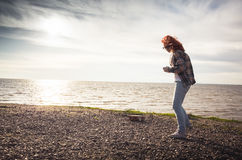 Girl walking on a sea coast Royalty Free Stock Image
