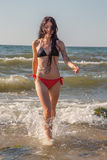 Girl walking in sea surf Stock Photography