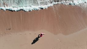 Girl walking on seashore.  Close up aerial top view of girl walking on beach. Woman in red outfit on coastline. Footprint in sand. stock footage