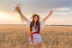 Girl walking with sheaf on wheat field at sunset, touching the e Royalty Free Stock Photo