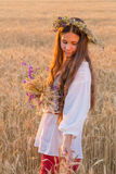 Girl walking with sheaf on wheat field at sunset, touching the e. Young girl walking with sheaf on ripe wheat field at sunset and touching the ears, outdoors Stock Images