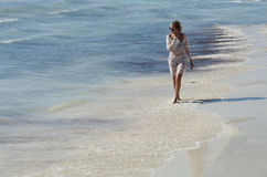 Girl walking on the shore. Blonde girl with glasses walking on the shore royalty free stock images