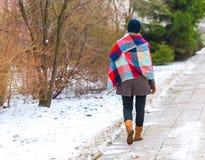 Girl walking by sidewalk at winter Royalty Free Stock Image