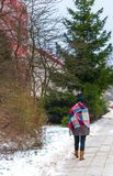 Girl walking by sidewalk at winter Stock Photo