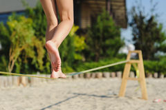 Girl walking on the sling. Child balancing on slackline at a beach. Shadow of a human figures on the sand Stock Photos