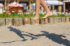Girl walking on the sling. Child balancing on slackline at a beach. Shadow of a human figures on the sand Royalty Free Stock Images