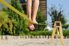 Girl walking on the sling. Child balancing on slackline at a beach. Shadow of a human figures on the sand Stock Photography