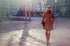 Girl walking and smiling in the city. With sun in the background Royalty Free Stock Photos