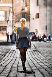 Girl walking on the street in the city wearing a skirt. Back. Stock Image