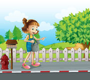 A girl walking in the street with a sprinkler Stock Images