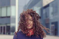Girl walking on the street and the wind messed up her hair Royalty Free Stock Photos