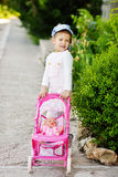 Girl walking with  stroller Royalty Free Stock Photography