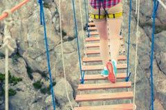 Girl walking on the suspension bridge. Hipster girl walking on the suspension bridge - vintage colored Royalty Free Stock Photos