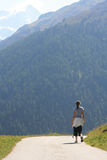 Girl walking in the swiss alps. Walking in the Valleys in the Swiss Alps during the summer months Royalty Free Stock Images