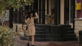 Girl walking and talking on the phone. Girl in a beige coat walking and talking on the phone stock footage