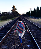 Girl walking on train tracks Stock Photos