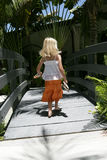 Girl walking in tropical scene. Young blond haired girl walking barefoot over bridge in tropical scene, holding sandals in hands Royalty Free Stock Photos