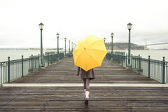 Girl walking with umbrella. Pretty African American girl walking with umbrella on the pier in San Francisco Royalty Free Stock Photo