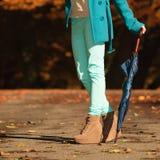 Girl walking with umbrella in autumnal park Stock Photos