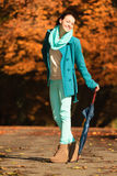 Girl walking with umbrella in autumnal park Stock Images