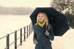Girl walking with umbrella on winter day. Woman with long blond hair on white snow landscape. Christmas and new year. Model smiling in grey coat, scarf and Royalty Free Stock Photos