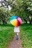 Girl walking under the big colorful rainbow-umbrella in the blooming garden. Spring, outdoors. Spring beauty concept. Freshness in blooming garden. Girl walking stock photography