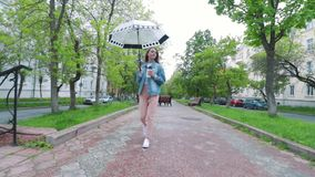 Girl walking under an umbrella in the rain stock video footage