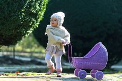 Girl walking with vintage doll stroller on sunny day stock photography