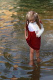 Girl walking in a water. Little girl that is walking in the river royalty free stock photos